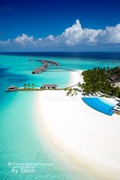 Photo aérienne de Velassaru Maldives. Vue sur la piscine a débordement, la page et le lagon de l'ile hôtel