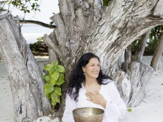 Jacqueline Bourbon at Soneva Fushi with a traditional Tibetan Bowl for Sound Healing.