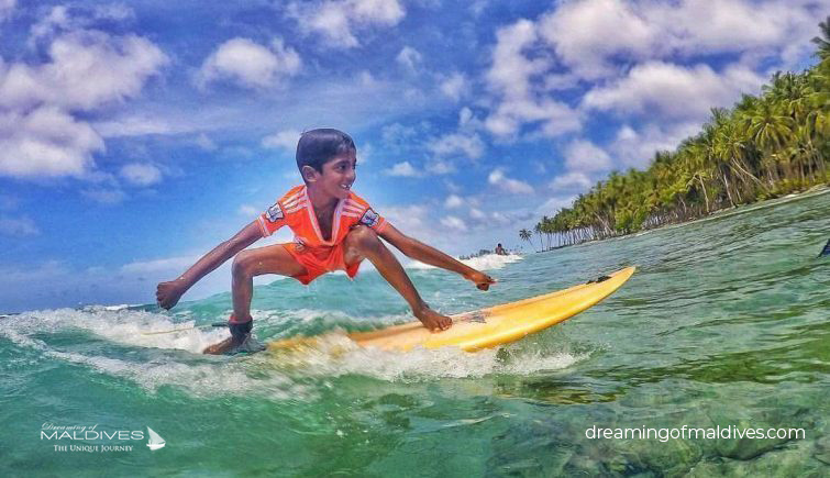 young boy Surfing in Maldives.